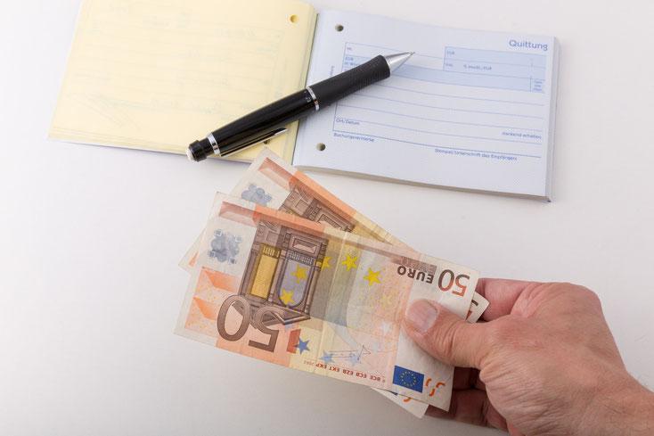 Mann hält 2 50-€-Scheine in der Hand, davor ein leerer Quittungsblock. Kurtz Detektei Stuttgart.