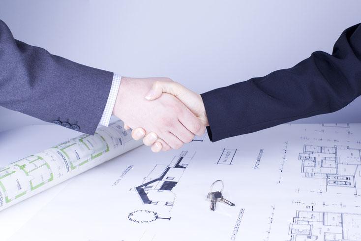 Zwei Männer schütteln sich über Bauplänen die Hände; Kurtz Detektei Stuttgart