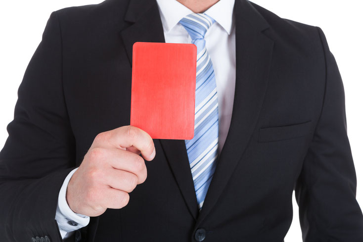 Mann im Anzug hält Rote Karte nach vorn; Mitarbeiterüberwachung Münster, Detektiv Münster, Wirtschaftsdetektiv Münster