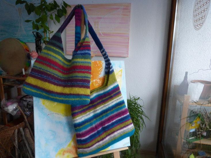 2 gefilzte Taschen mit unterschiedlich langen Gurten über einem Engelbild 60 x 60 cm