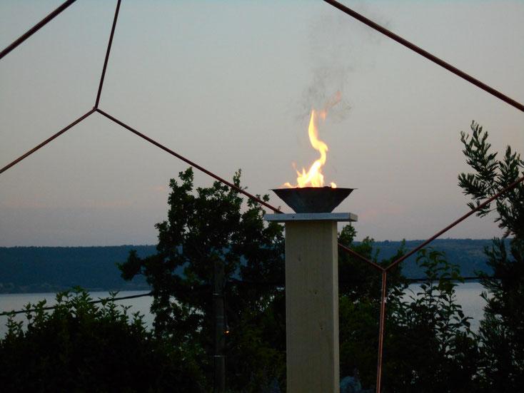 Foto: Dodekaeder aus Kupfer, Aufbau im Garten mit stimmungsvoller Feuerschale und Seekulisse