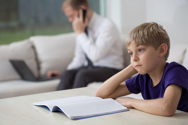 Kind sitzt traurig vor leerem Heft, währen der Vater im Hintergrund telefoniert und am Laptop tippt; Kurtz Detektei Hamburg.