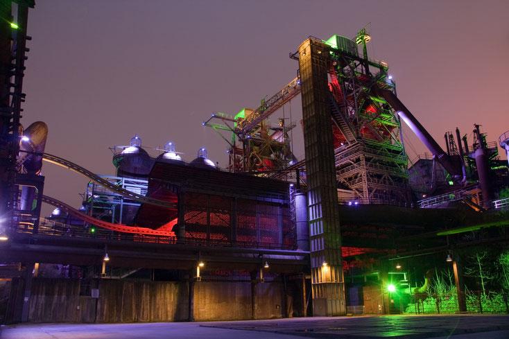 Ehemaliges Thyssen-Hüttenwerk im Landschaftspark Duisburg-Nord, bunt illuminiert bei Nacht; Kurtz Wirtschaftsdetektei Duisburg