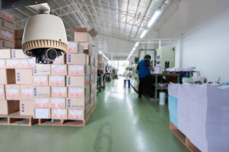 Eine Videoüberwachungskamera in einem Warenlager, im Hintergrund Kartons und ein Arbeiter; Kurtz Detektei Duisburg