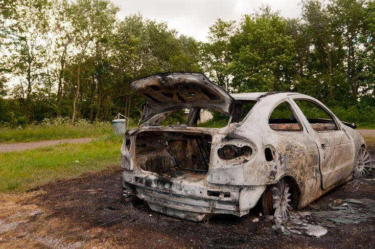 Ein ausgebrannter weißer 2-Türer auf einer Wiese, vermutlich Opel; Detektive der Kurtz Detektei Duisburg