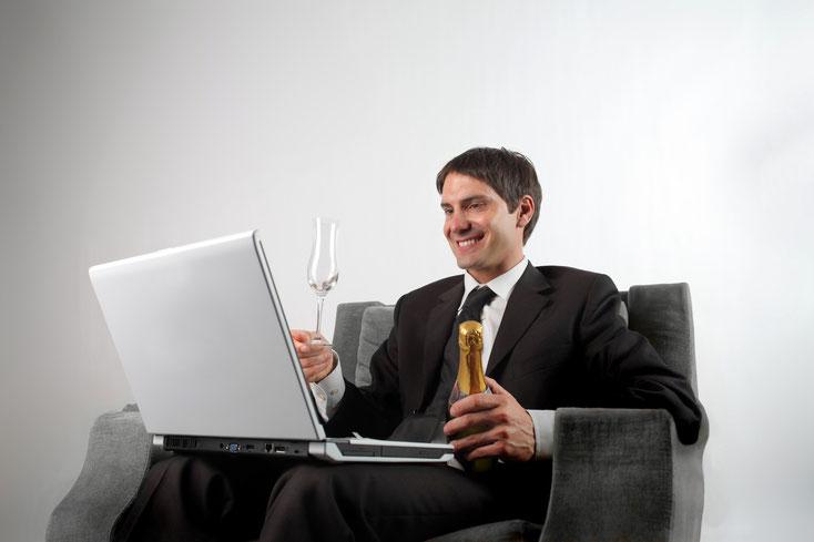 Mann im Anzug sitzt grinsend mit Champagner und Laptop in einem Sessel; Wirtschaftsdetektive in Duisburg, Kurtz Detektei Duisburg