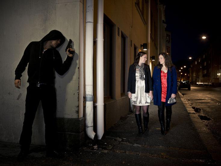 Mann wartet mit gezogener Waffe hinter einer Gebäudeecke auf zwei sich nähernde Frauen; Kurtz Detektei Duisburg.