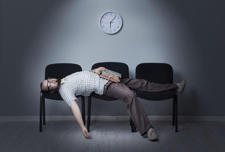 Mann liegt mit Aktenordner in der Hand schlafend auf Stühlen, über ihm eine Uhr; Kurtz Detektei Duisburg