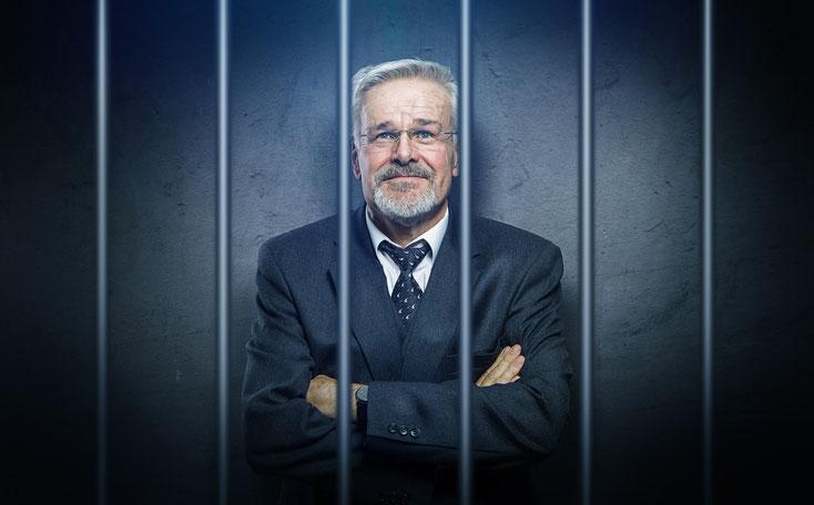 Geschäftsmann im Anzug höhnisch grinsend hinter Gittern.