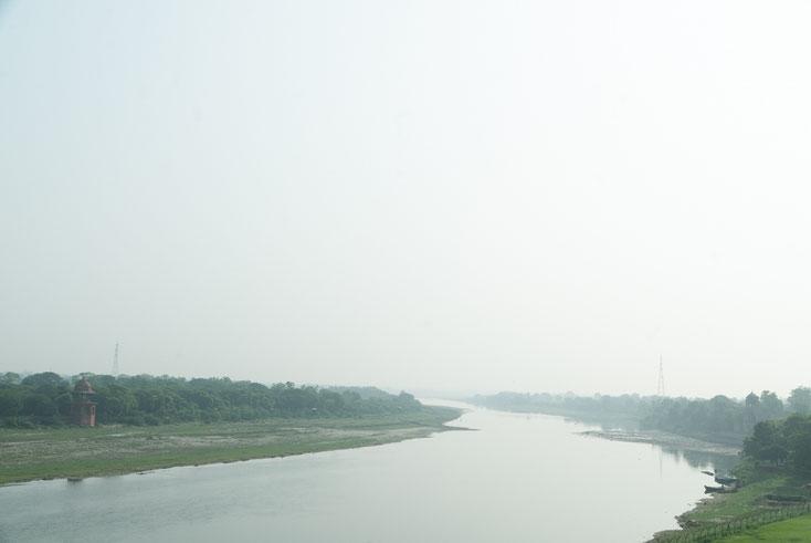 Breiter Fluss bei diesigem Wetter mit grünem Ufergebüsch
