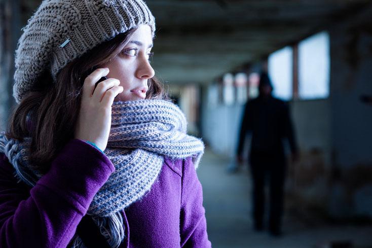 Junge Frau mit Handy, im Hintergrund ein Verfolger im Schatten; Kurtz Detektei Hamburg