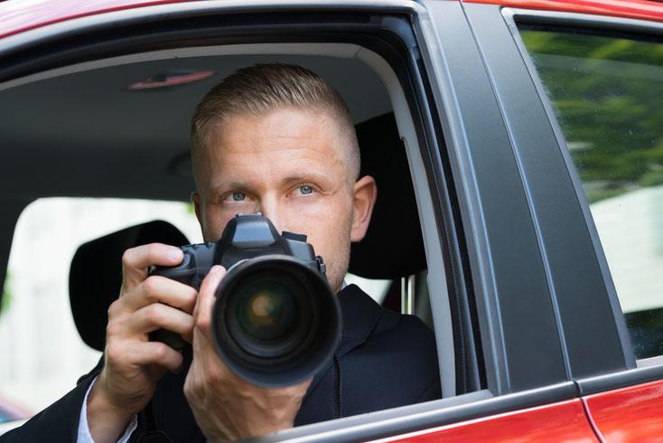 Ein Mann im Anzug sitzt im Auto, blickt durch das offene Fenster nach draußen und hält eine Spiegelreflexkamera in beiden Händen: Wirtschaftsdetekive der Kurtz Detektei Hamburg.