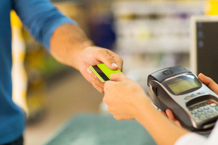 Mann übergibt Kassierin eine Zahlungskarte; Kurtz Detektei Hamburg.
