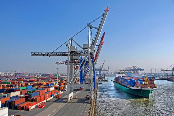 Containerterminal Hafen Hamburg, ein Containerschiff zu Wasser, dazu zahlreiche zwischengelagerte Container und Kräne; Kurtz Detektei Hamburg