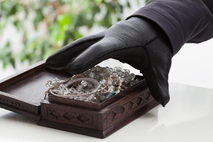 Dieb mit Handschuh greif in eine Schmuckschatulle. Detektive der Kurtz Detektei Hamburg klären auf.