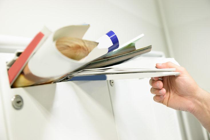 Voller Briefkasten, jemand versucht, einen weiteren Brief hineinzustecken. Kurtz Detektei Hamburg, Schuldnersuche.