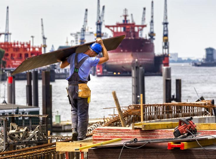 Bauarbeiter schleppt eine Platte im Hamburger Hafen zu einer Baustelle, im Hintergrund Schiffe und Kräne; Kurtz Detektei Hamburg.