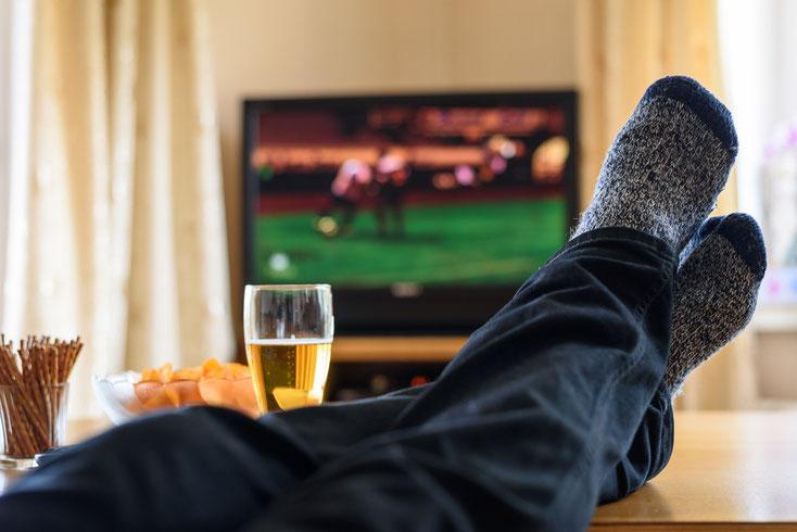 Männerfüße in Strümpfen auf einem Couchtisch, darüber eine lockere-Jeanshose, im Hintergrund läuft Fußball auf einem Fernseher; Bier, Chips und Salzstangen stehen auf dem Tisch; Kurtz Wirtschaftsdetektei Düsseldorf