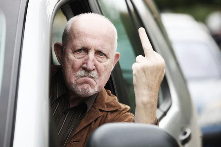Älterer Mann sitzt im Auto, hält den Kopf aus dem Fenster und zeigt mit wütendem Gesichtsausdruck den Mittelfinger; Kurtz Detektei Düsseldorf Halterermittlung