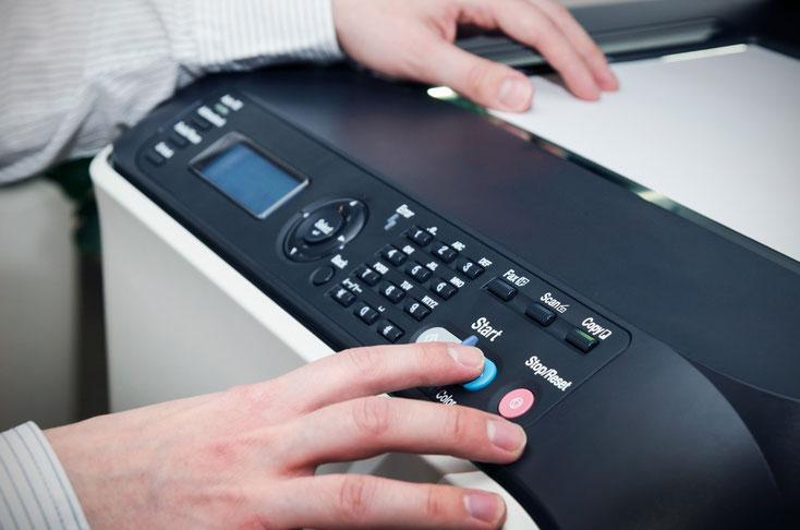 Ein Mann kopiert an einem Multifunktionsgerät Dokumente; Betriebsspionage, Kurtz Wirtschaftsdetektei Düsseldorf