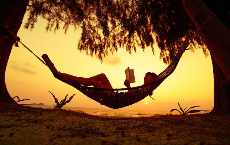 Frau liegt am Strand in einer Hängematte und liest im Sonnenuntergang ein Buch; Kurtz Detektei Düsseldorf.