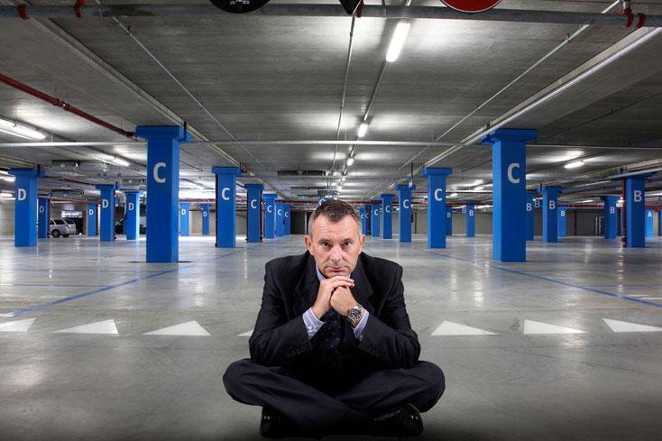 Ein Mann sitzt deprimiert auf einem leeren Parkplatz in einer Tiefgarage; Kurtz Detektei Düsseldorf