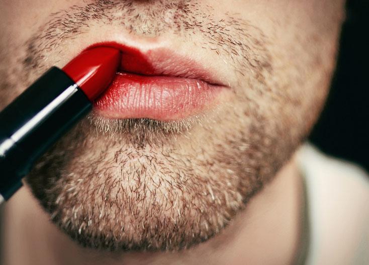 Mann mit Dreitagebart trägt roten Lippenstift auf; Kurtz Detektei Düsseldorf.