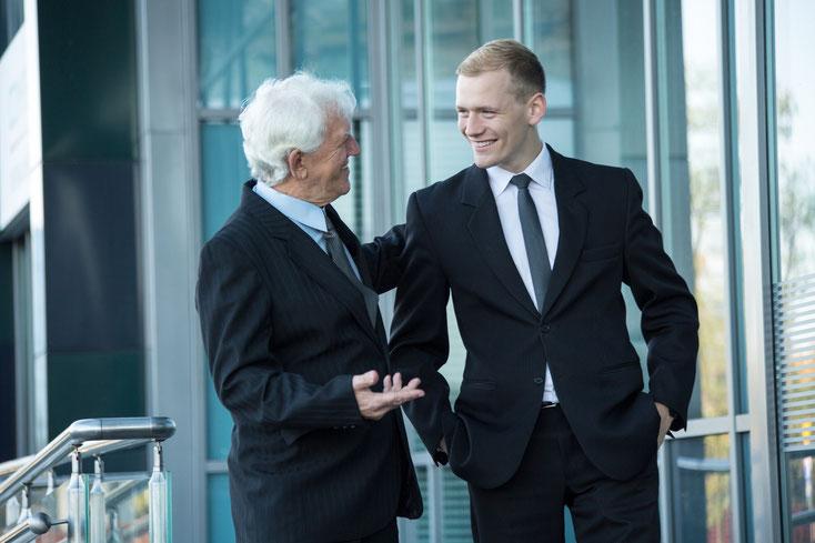 Ein alter und ein junger Geschäftsmann in Anzügen vor einem Bürokomplex, beide lachen; Kurtz Detektei Düsseldorf