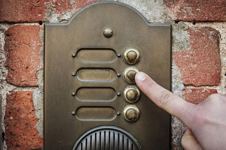 Mann hält seinen Zeigefinger an den Klingelknopf einer unbeschrifteten Klingeltafel, das Gebäude ist renovierungsbedürftig; Kurtz Detektei Düsseldorf.