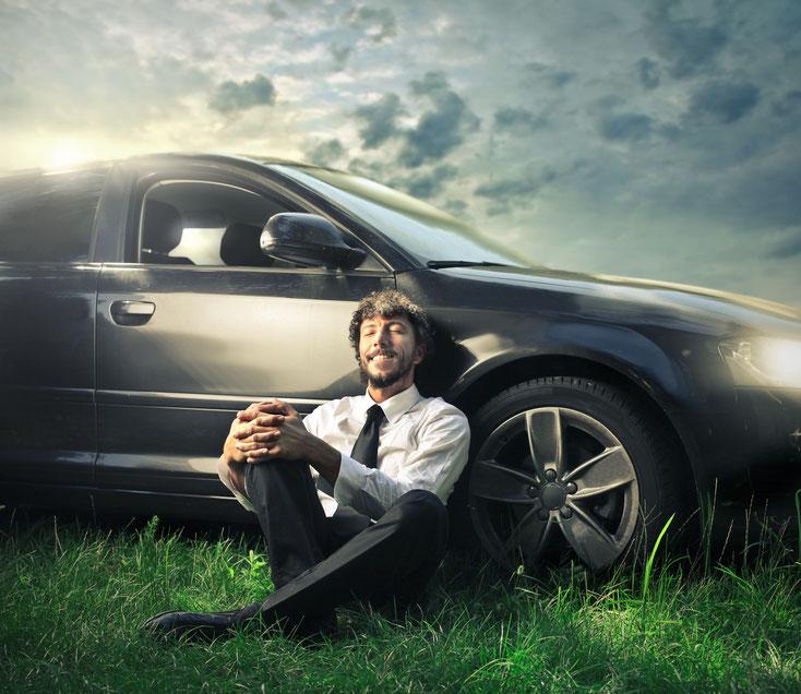 Mann im Anzug sitzt mit zufriedenem Lächeln und geschlossenen Augen im Gras, den Rücken an ein laufendes Auto gelehnt; Abrechnungsbetrug Kurtz Detektei Düsseldorf
