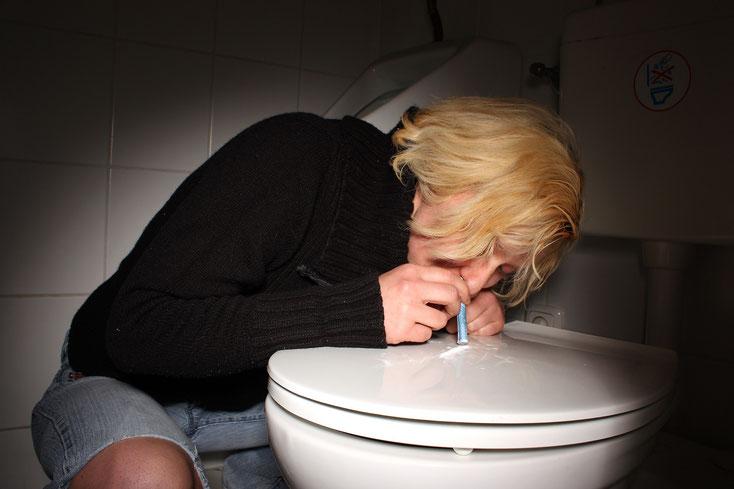 Frau konsumiert auf dem Toilettendeckel nasal Drogen, Kurtz Detektei Köln.