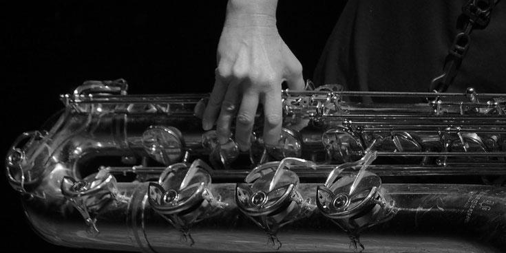 Anne Wiemann hält ein Bariton Saxofon in der Hand und erklärt, wie man greift