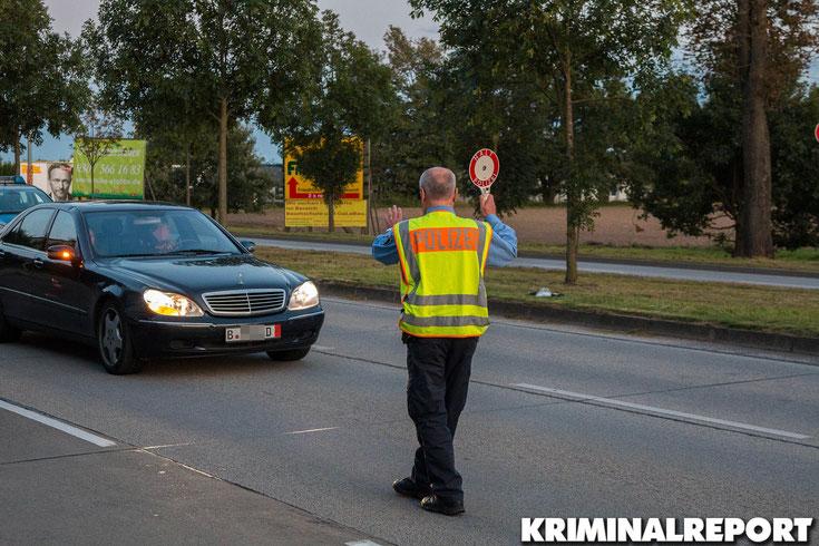 Ein Beamter signalisiert dem Mann, dass er halten soll.|Foto: Christopher Sebastian Harms