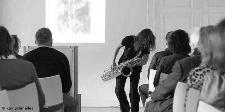 Anne Wiemann spielt Bariton Saxofon und geht dabei geht dabei gleichzeitig durch die Zuschauerreihen