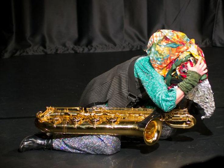 Anne Wiemann hat eine riesige Vogelmaske auf dem Kopf. Sie kniet auf der Bühne, vor ihr liegt ein Bariton Saxofon