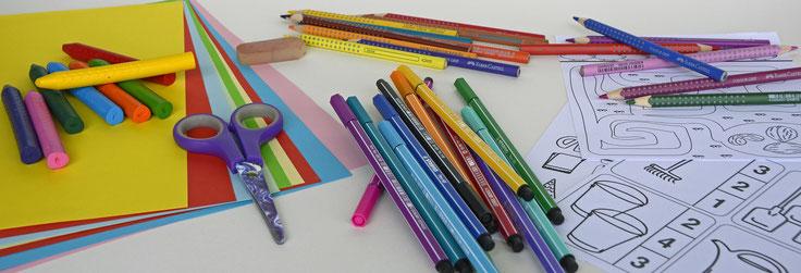 Flyer: Holzisch auf dem Stifte, Kreide, Wassermalfarben, Lineal, Zirkel, Kleber und anderer Bedarf liegt