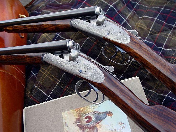 A pair of fine 20 gauge side by side shotguns, finely engraved with scenes after Archibald Thorburne and English Fine Scroll