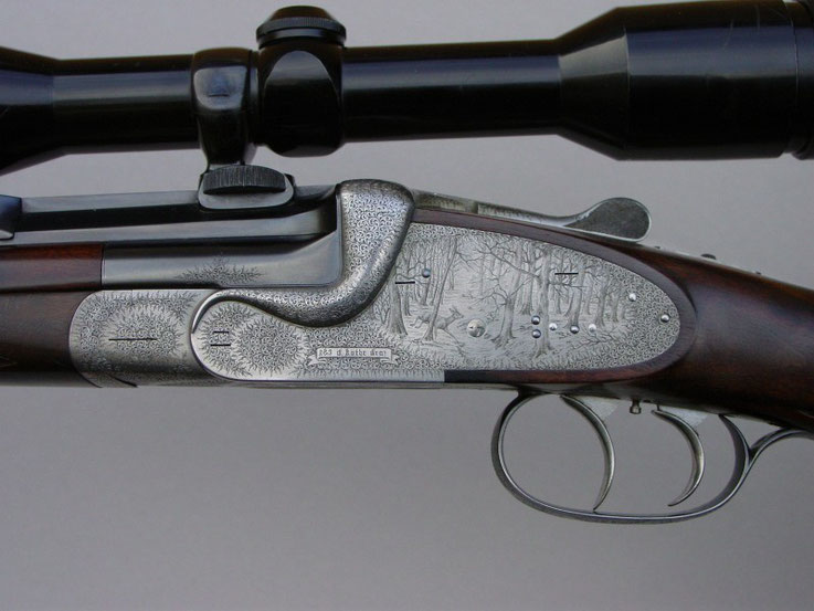 A break action single barrel rifle engraved with English Fine Scroll and game scenes with roe deer