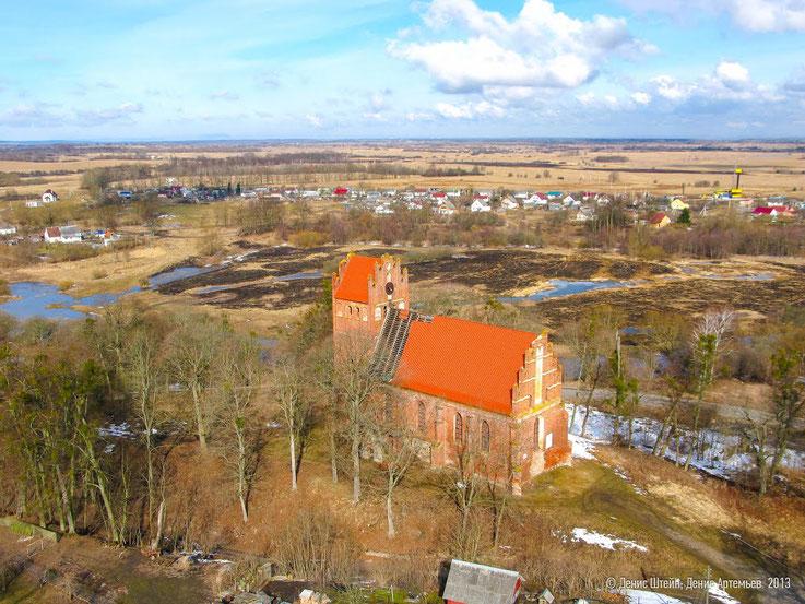 Vogelperspektive auf die Ännchen Kirche. Im Hintergrund zwischen Himmel und Erde, dass Brandenburger Haff.
