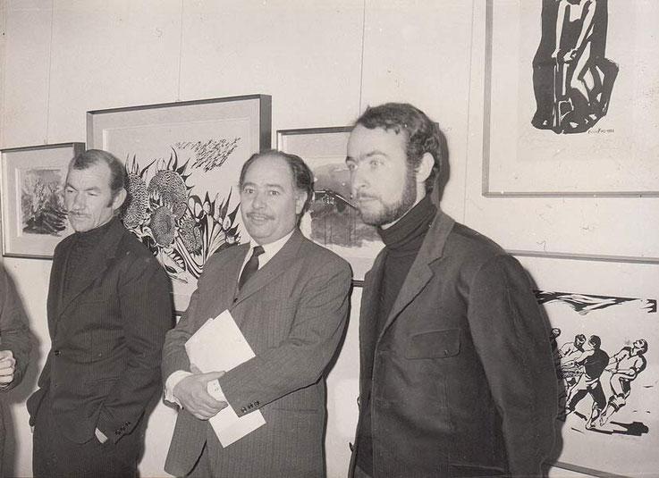 Da sinistra Piccinnu noto Cinquantasei con Foiso Fois e Lino Pes all'inaugurazione della Galleria Guernica.                         Nello sfondo alcune opere di Foiso Fois.