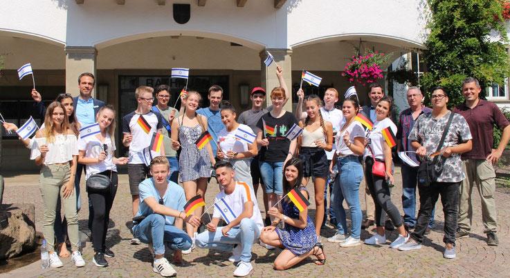 Eine deutsch-israelische Jugendgruppe mit Fähnchen vor dem Rathaus in Attendorn