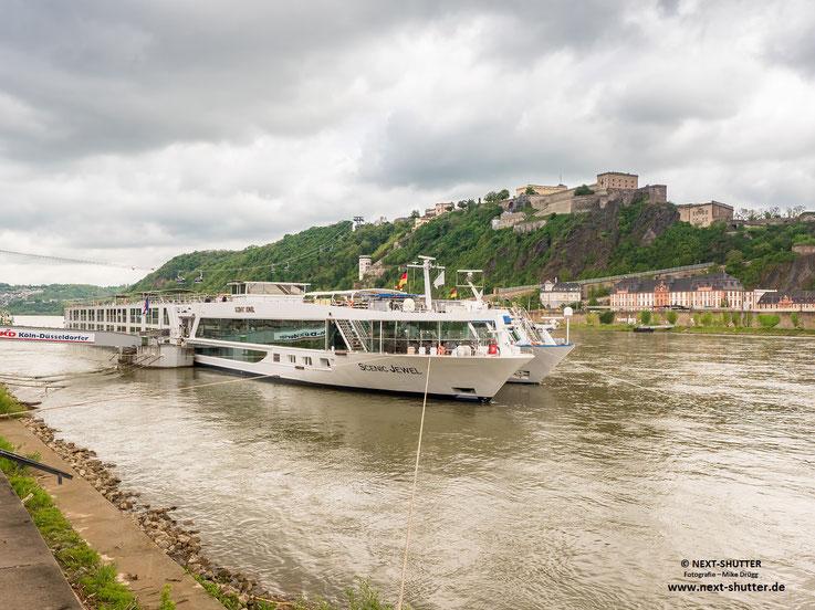 Die Festung von der anderen Rheinseite gesehen, davor zwei Fluss - Kreuzfahrtschiffe.  Es sind übrigens Unmengen davon unterwegs, dagegen ist die Anzahl der Kreuzfahrtschiffe in Hamburg geradezu überschaulich. Aber die sind ja auch ein bisserl größer.
