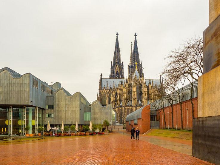 Der Dom bei Tag, links das Museum Ludwig. Unter dem rot gepfaltsterten Platz befindet sich die Philharmonie, weshalb man bei Konzerten diesen Platz nicht betreten darf. Es wirkt schon skuril wenn ein leerer Platz von Sicherheitspersonal bewacht wird.