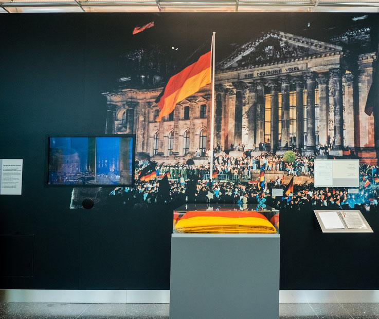 """Am 3. Oktober 1990 vereinigen sich die beiden deutschen Staaten. Die erstmals aufgezogene """"Flagge der Einheit"""" liegt jetzt hier im Museum. Sie ist mit rund 60 qm wahrscheinlich die weltweit größte Deutschlandflagge."""