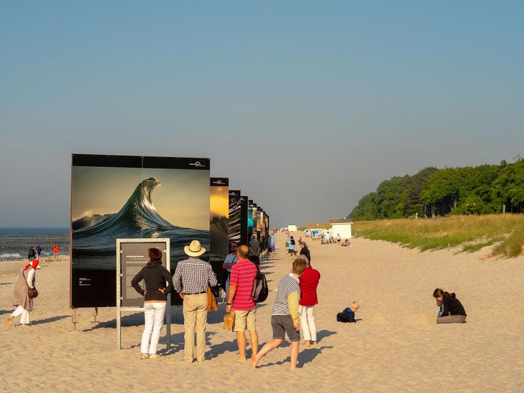 Die am Strand aufgebaute Fotoausstellung wurde durch die Betrachter zum guten Motiv.