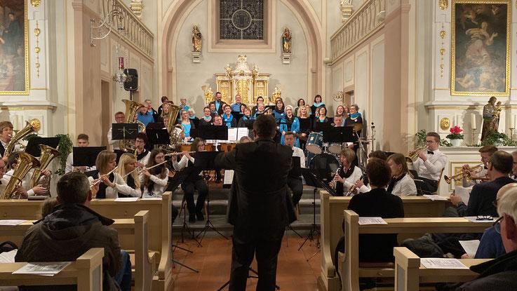Dirigent leitet Konzert mit Chor und Musikkapelle