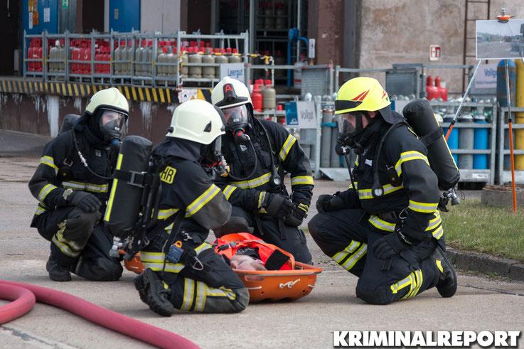 Feuerwehrleute retten eine Person aus dem Gefahrenbereich.|Foto: Christopher Sebastian Harms