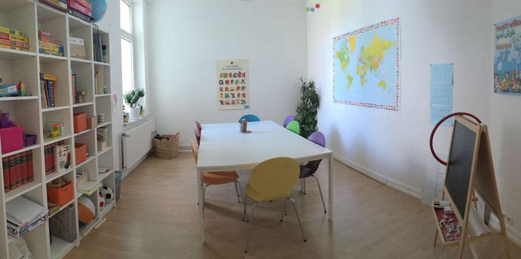 Auf dem Bild ist ein Lernförderraum der Lernpraxis Zeddies zu sehen. In dem Raum befindet sich links ein Tisch mit bunten Stühlen und rechts ein großes Regal mit verschiedenen Büchern, Spielen, Kartons und Lernmaterialien. Es sind zum Beispiel ein Ball, e