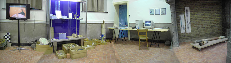 Objects and documents are scattered and reconstitute the workroom of an archaeologist.