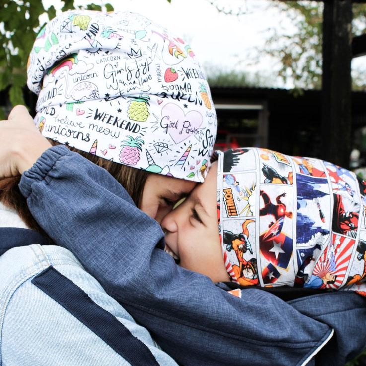 Vater trägt Sohn auf dem Arm bekleidet mit Designs von Stolze Helden, Rucksack und Beanie